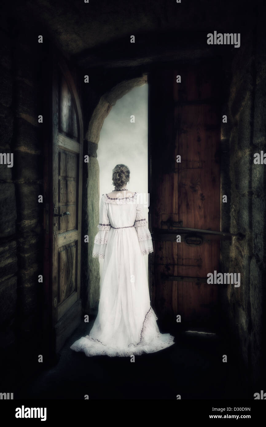 a woman in an elegant dress is standing in the gate of an old castle - Stock Image