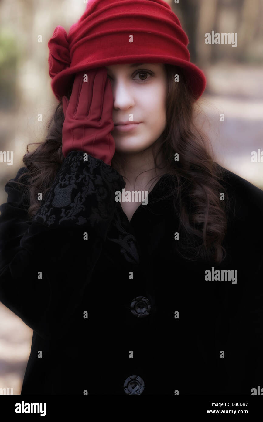 a beautiful young woman with a red hat and red gloves - Stock Image