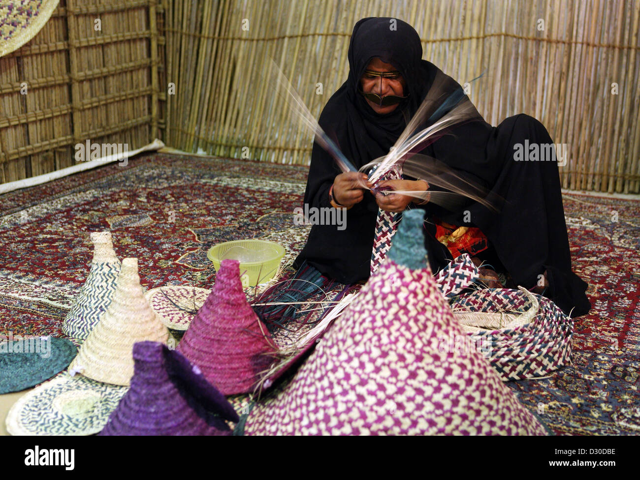 Dubai, United Arab Emirates, woman in national dress with raffia weaves Stock Photo