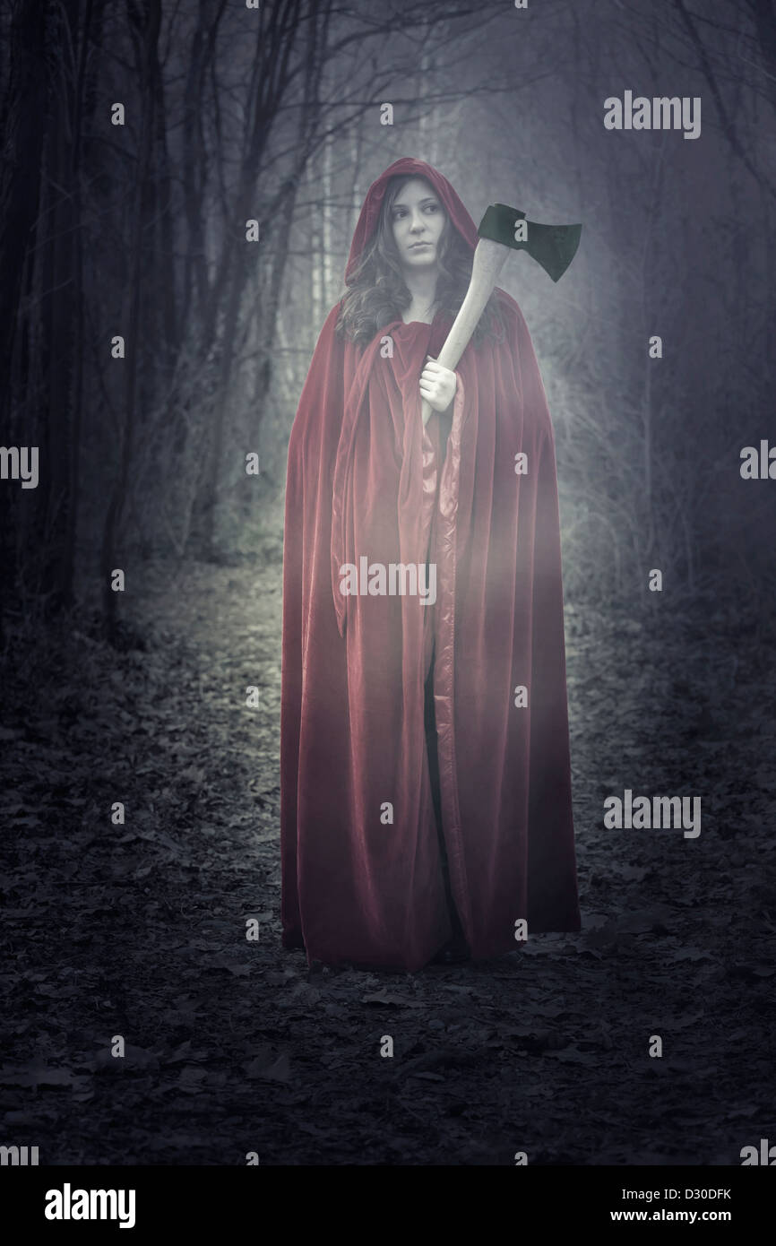 a woman in a red cloak with an axe - Stock Image