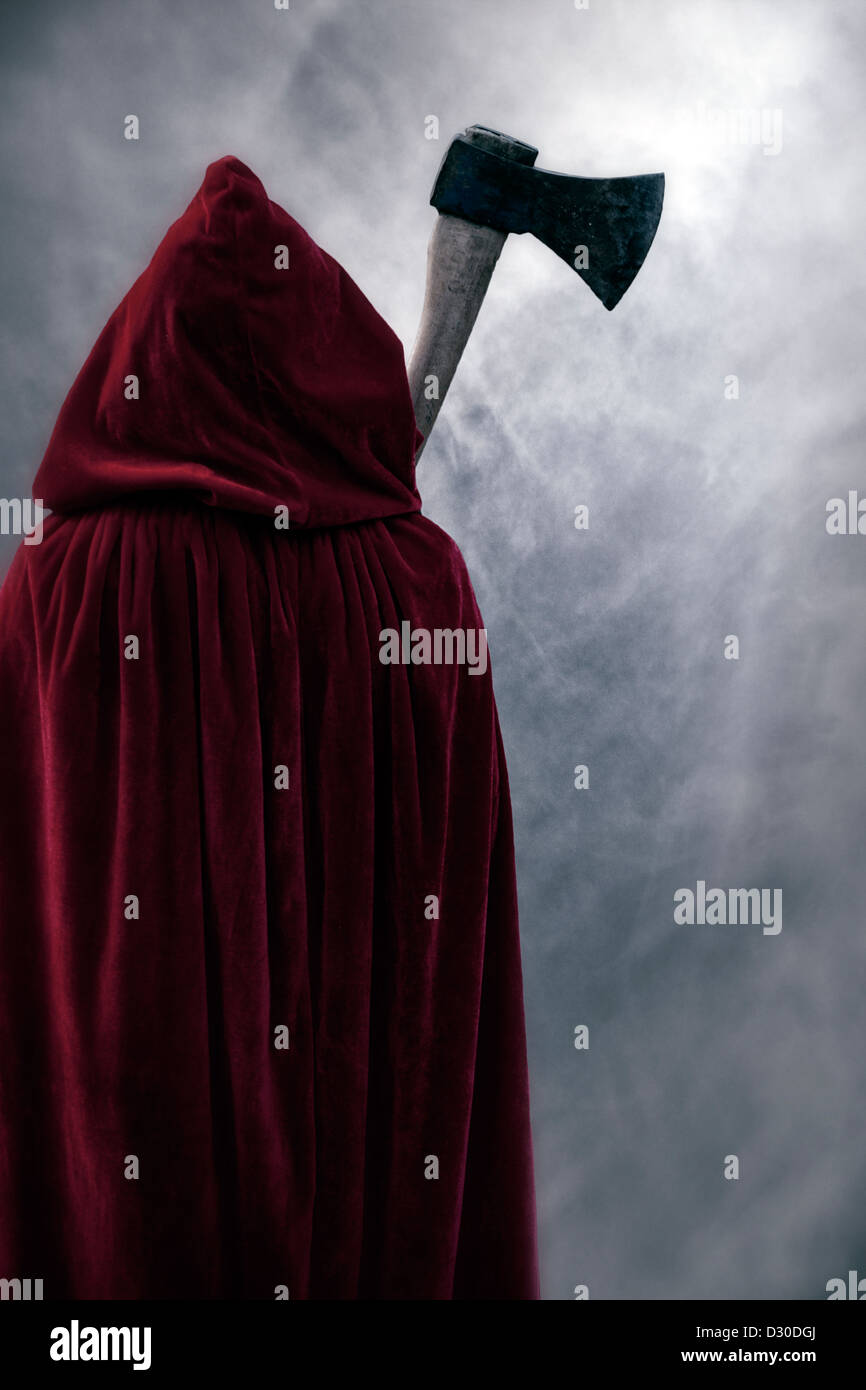 a guise in a red cloak with an axe - Stock Image