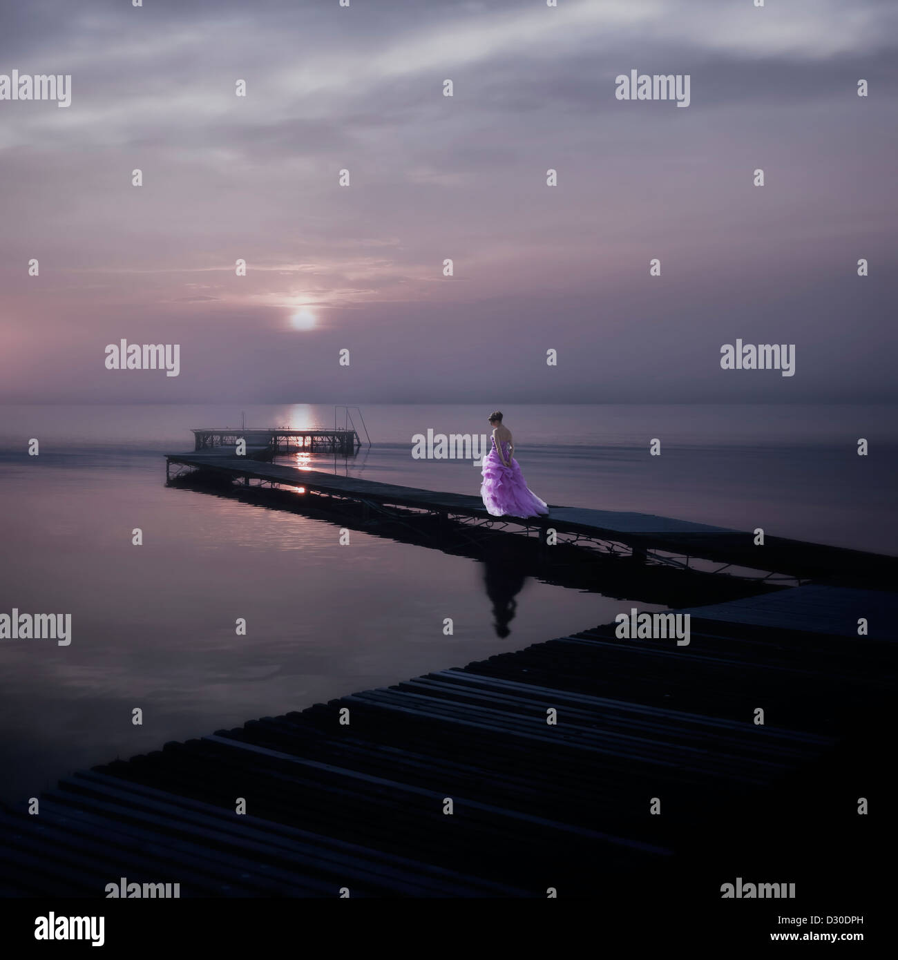 a woman in an elegant pink dress on a footbridge on a lake during sunset - Stock Image