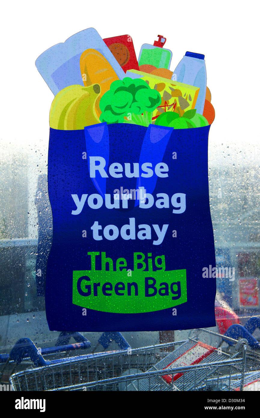 a reuse your big green bag sign outside a tesco supermarket - Stock Image