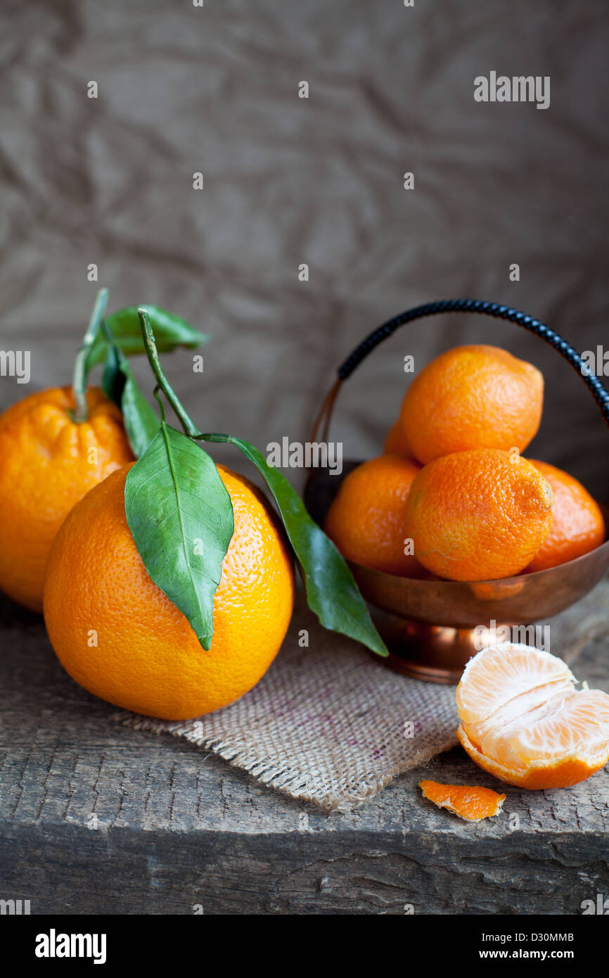 Still life: oranges with leaves, tangerines and slices of  on wooden table - Stock Image