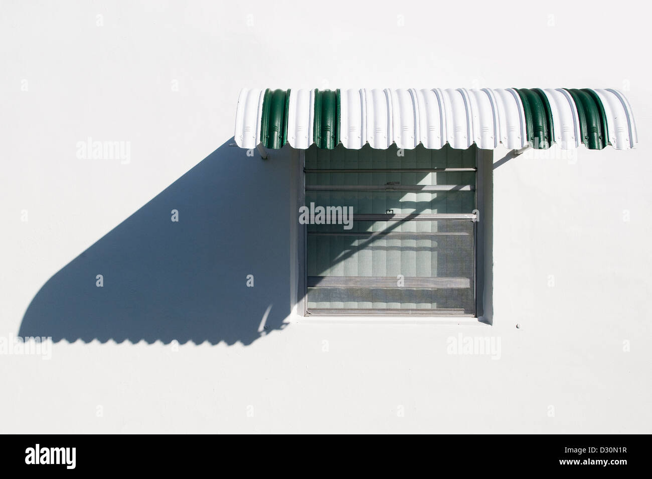 A window with mid-century metal-shutter/shade on a white walled house in a Florida retirement community. - Stock Image