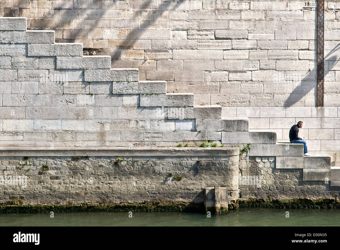 A man enjoys solitude along the River Seine, Paris, France. River height makers and the stone stairs provide bold - Stock Image