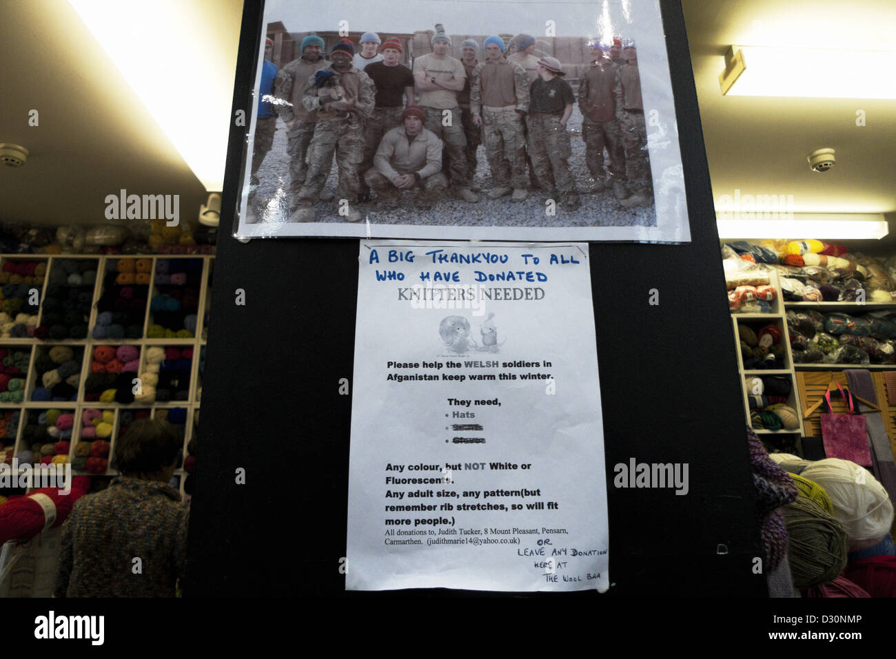 An ad calling for knitters to make hats for soldiers in Afghanistan in Carmarthen Market wool shop Carmarthenshire, - Stock Image