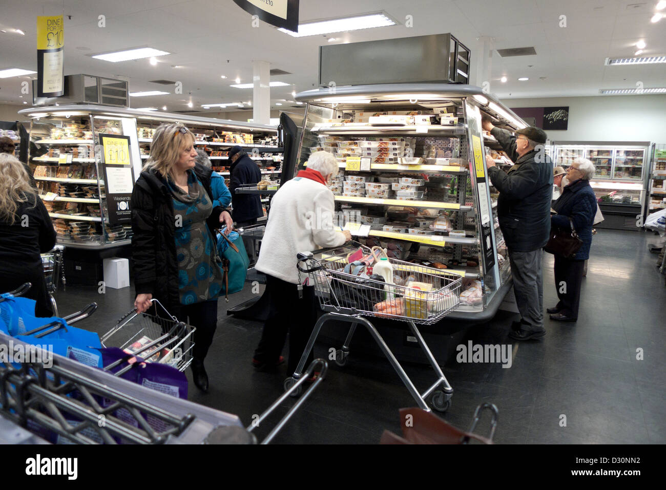 Customers with shopping basket and trolley looking at chilled food products on refrigeration aisle inside Marks - Stock Image