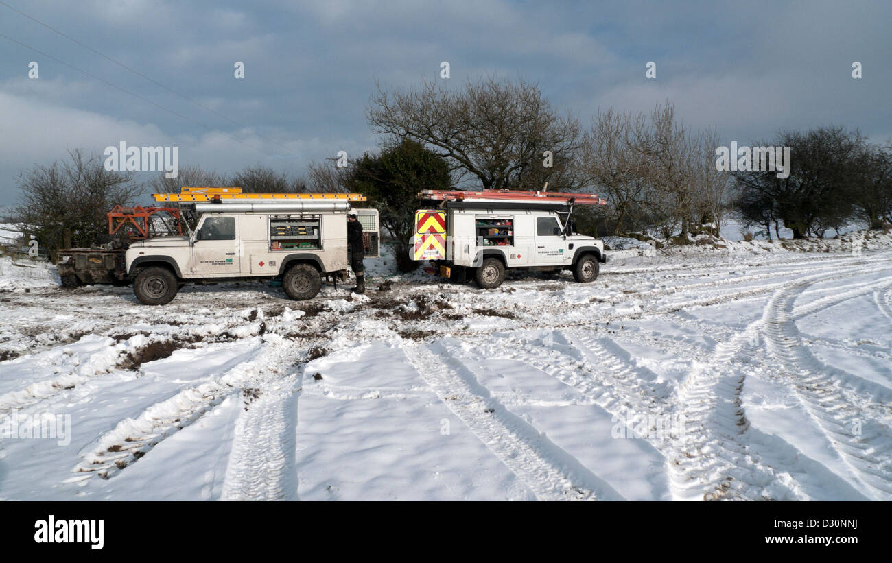 Western Power Distribution vehicles in snowy field on farm land Wales UK Stock Photo