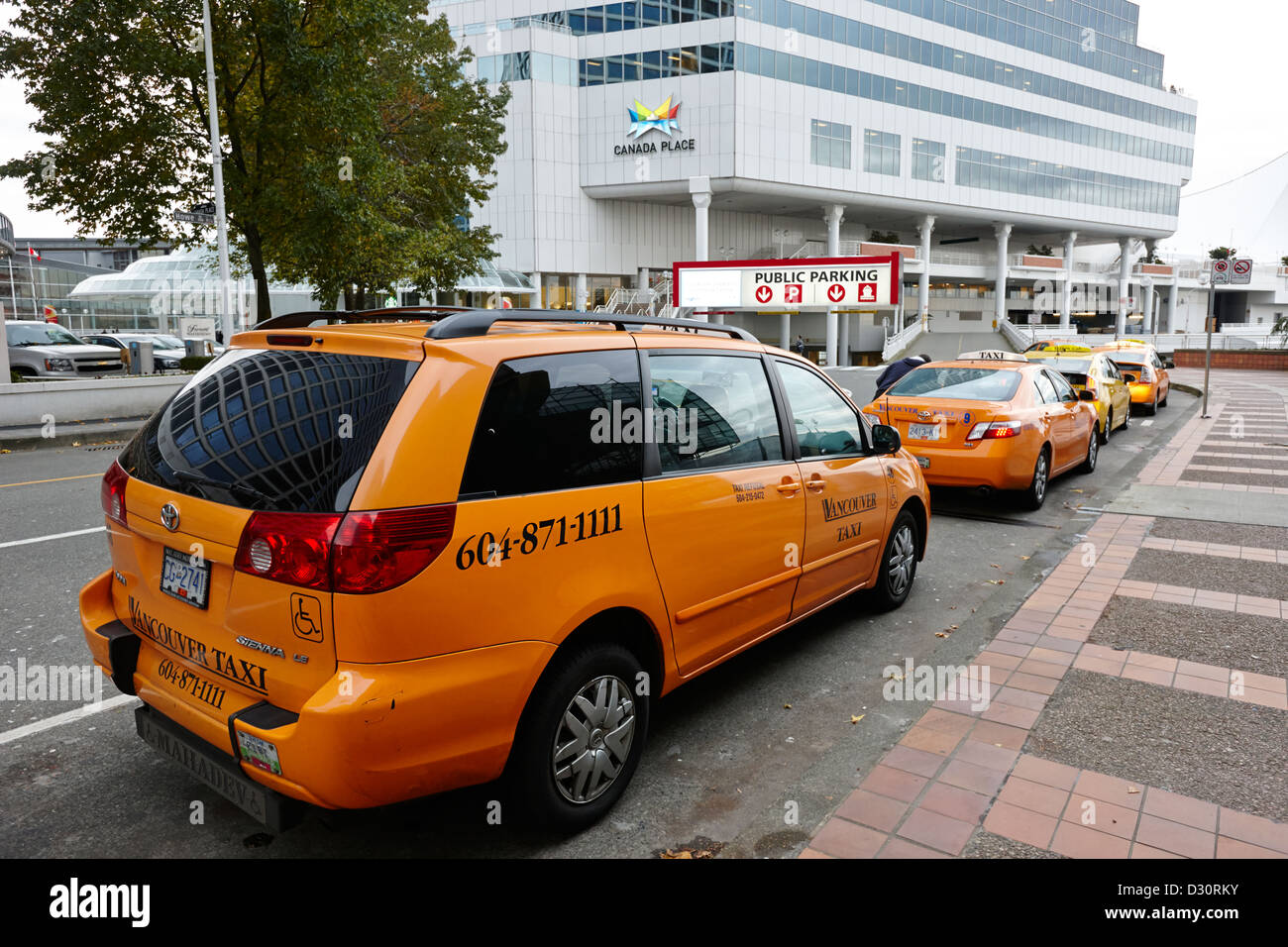 row of yellow cabs outside canada place Vancouver BC Canada - Stock Image