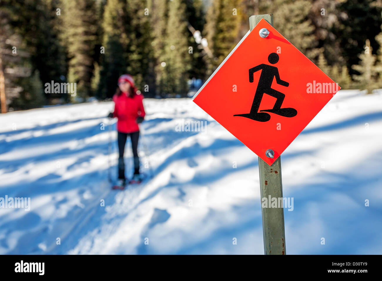 snowshoe trail sign with a snowshoer in the background - Stock Image
