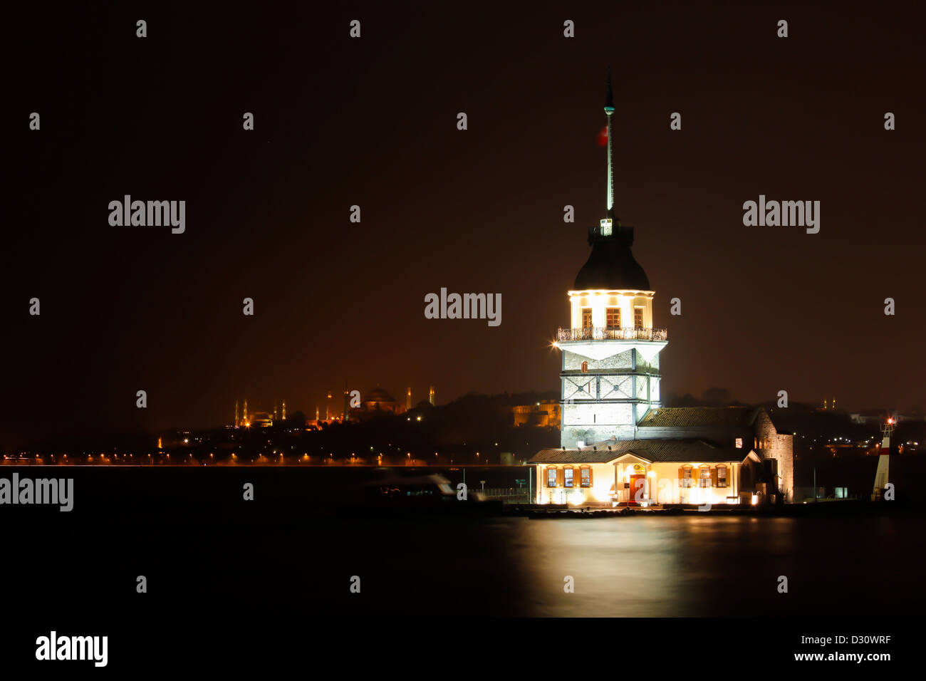 Maiden's tower floodlit at night with minarets of Hagia Sophia and Blue Mosque, Uskudar, Bosphorus strait, Istanbul, - Stock Image