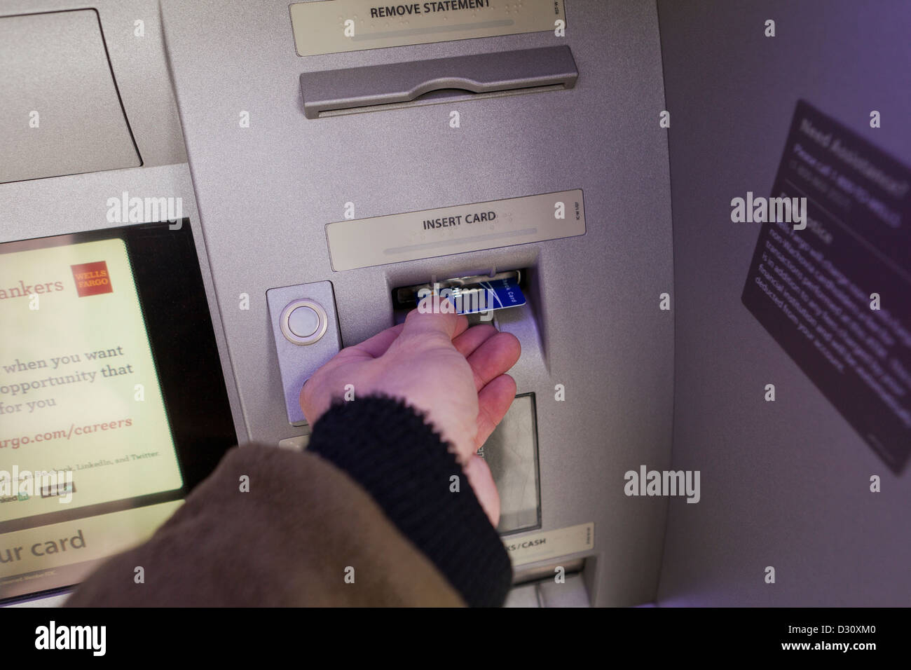 Man inserting bank card into ATM - Stock Image