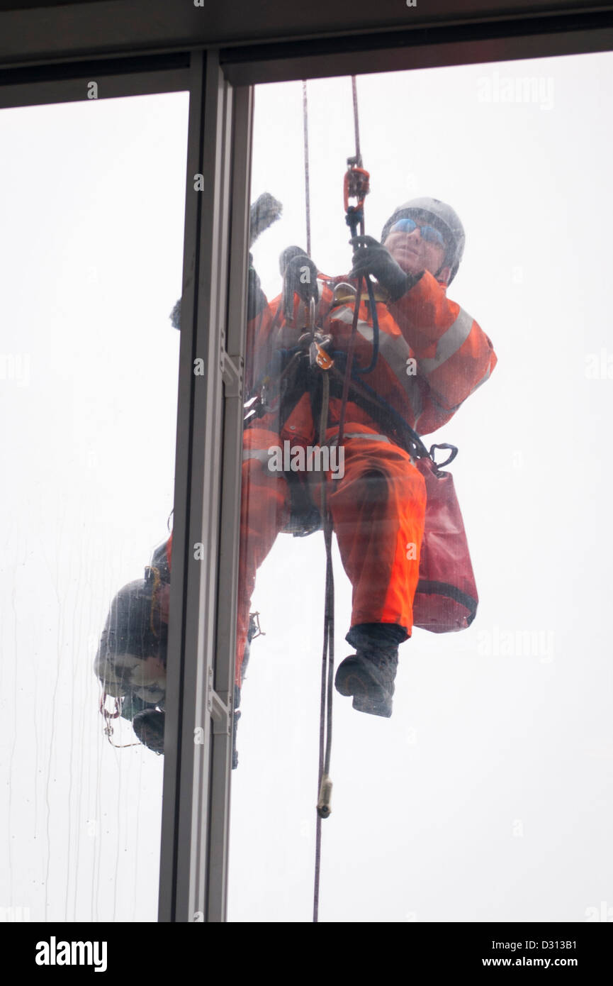 London City The Shard abseiling window cleaner outside 69th floor viewing deck cleaning windows with brush & - Stock Image