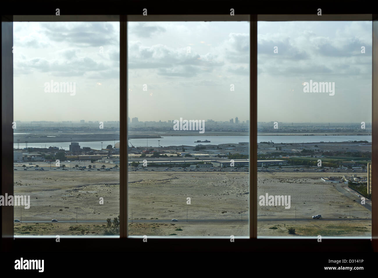 A barren field in Dubai seen through a window - Stock Image