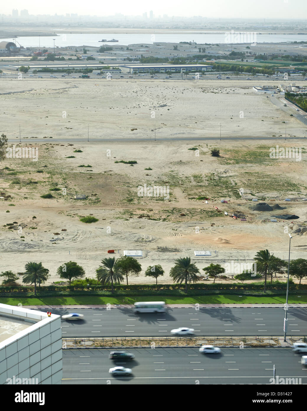 A barren field in Dubai with buzzing traffic nearby - Stock Image