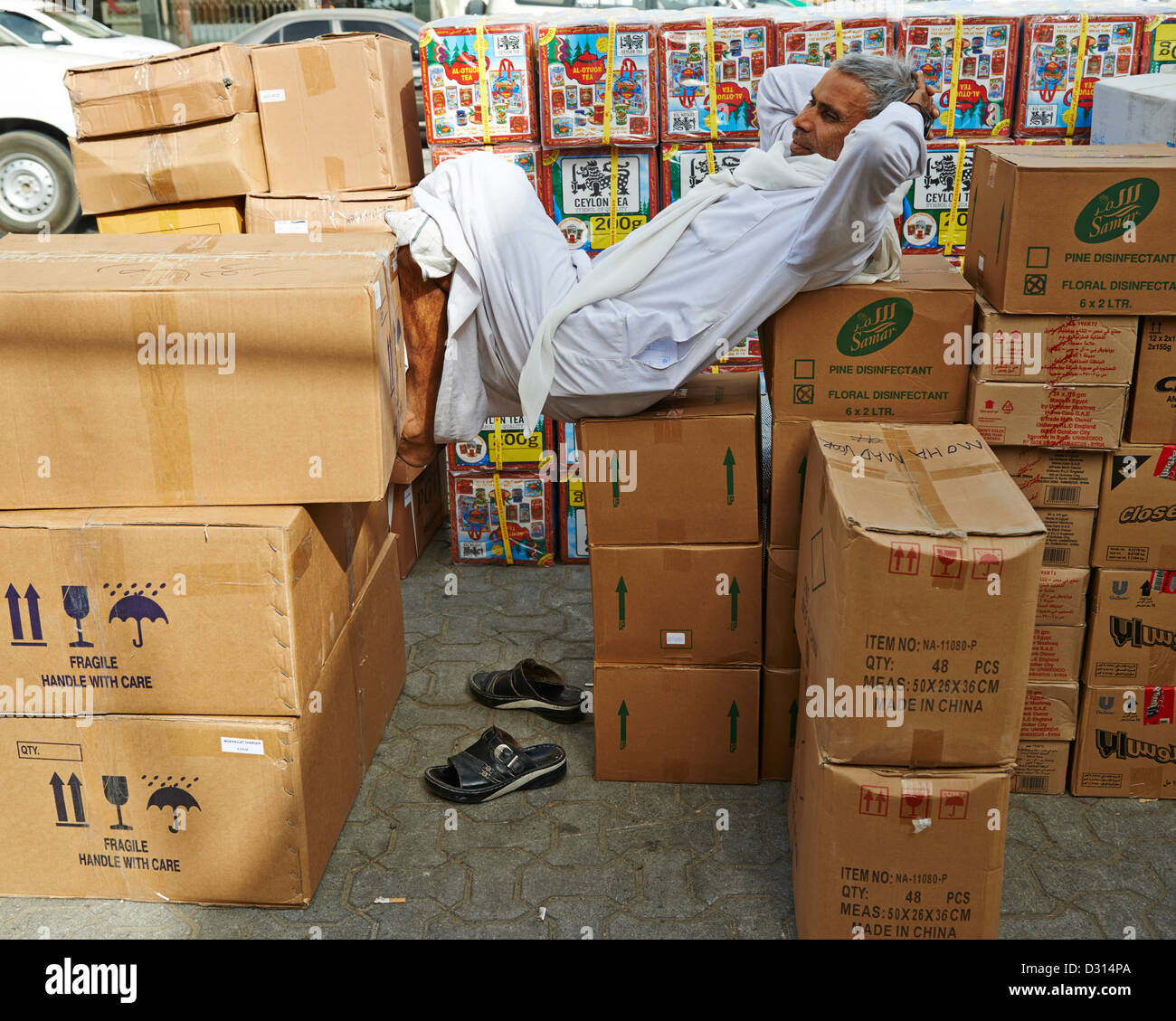 A man resting precariously on cardboard boxes - Stock Image
