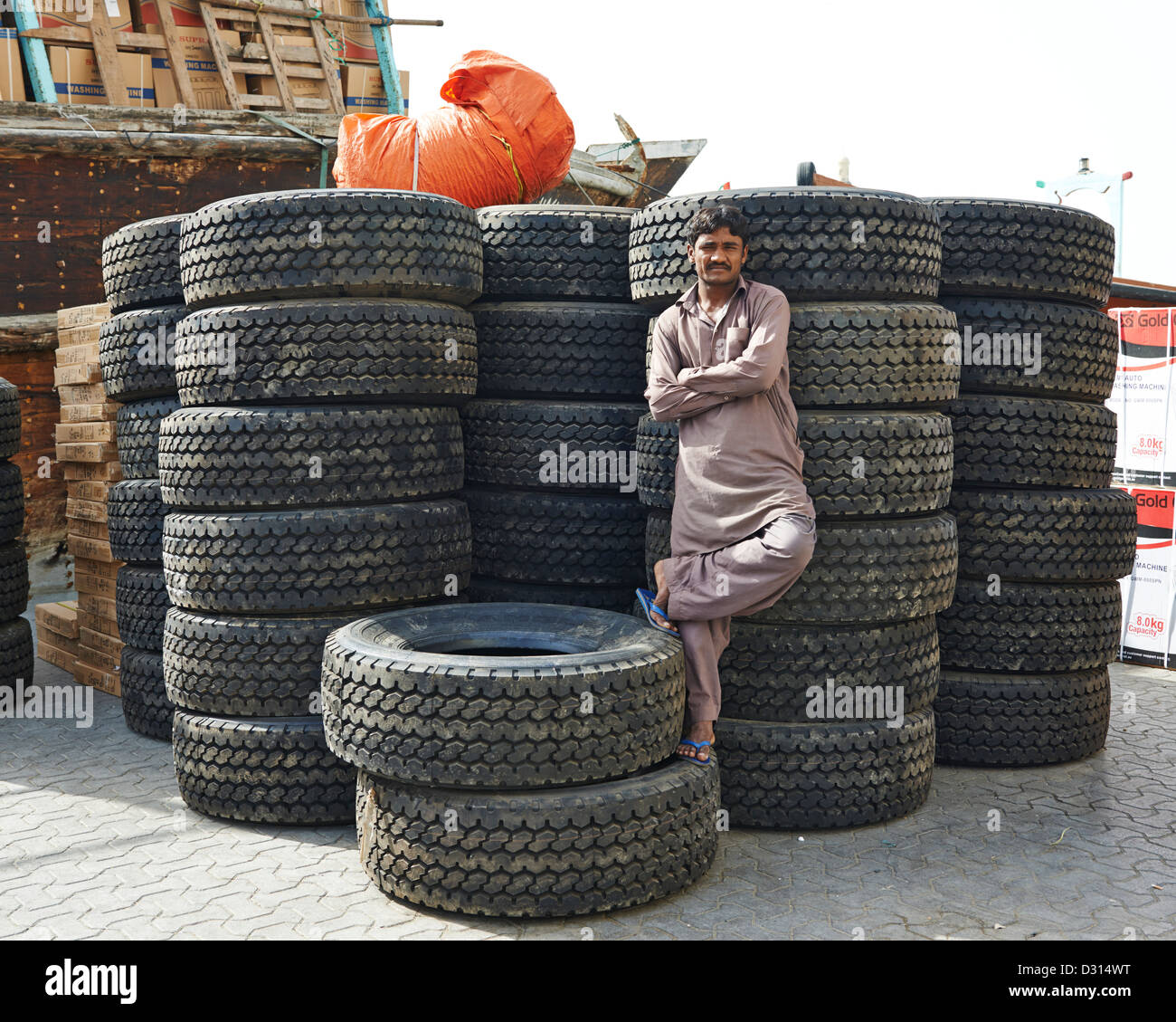 A man crosses his arm and raises his leg in front of a huge stack of tires - Stock Image