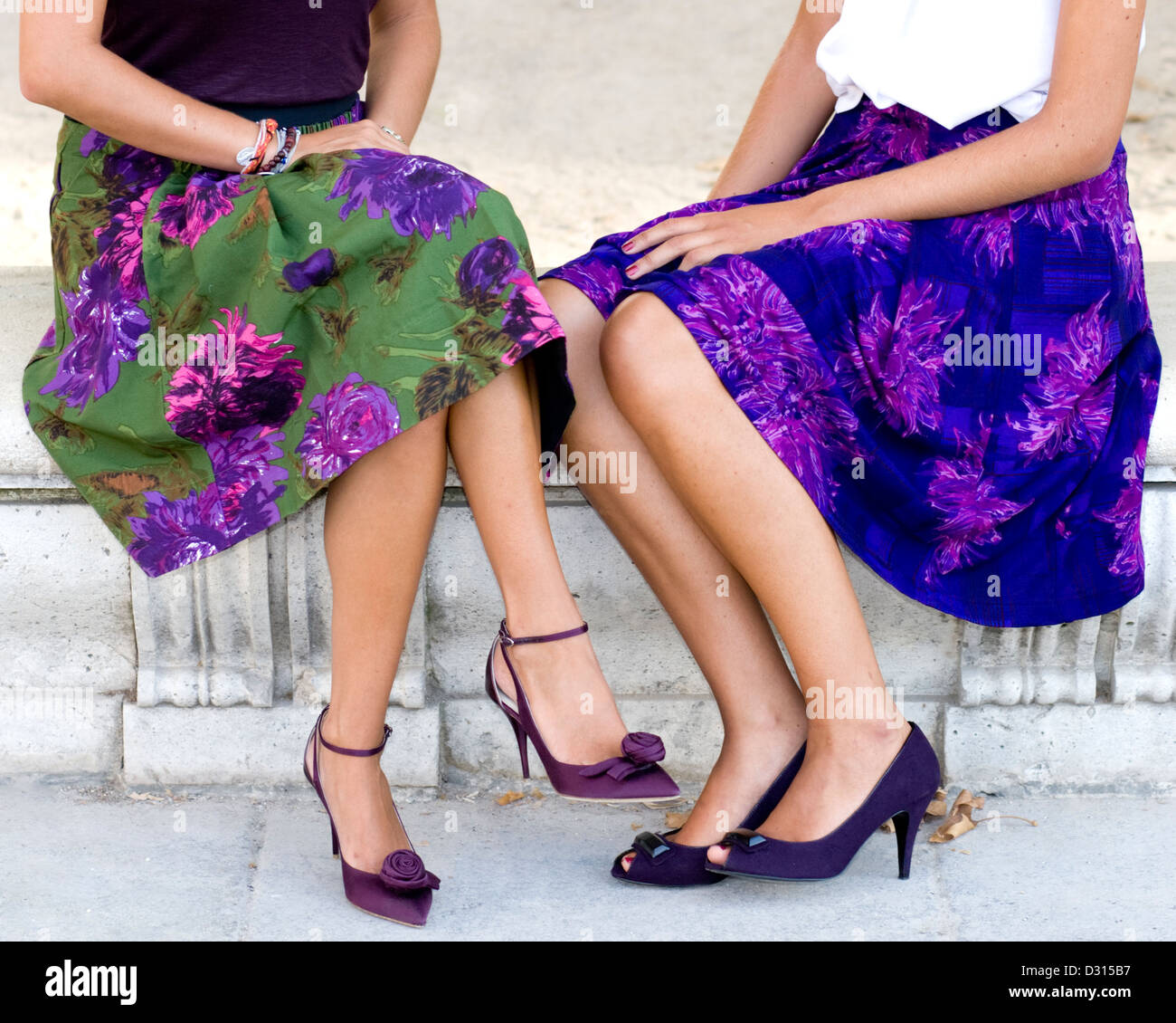 girls in flowery skirts high heeled shoes stone bench - Stock Image