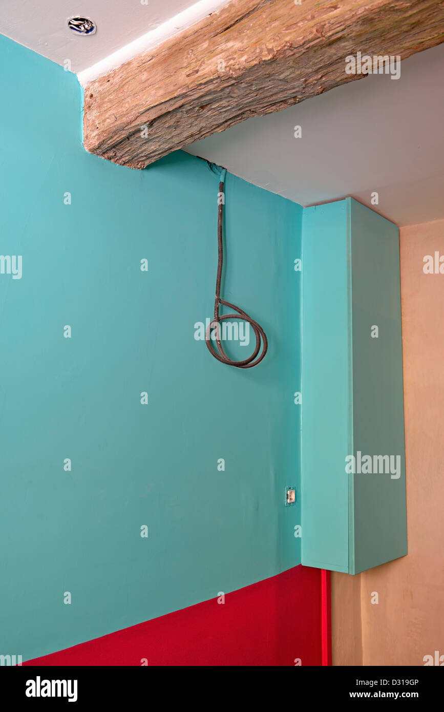 Wall with electricity cable hanging down - Stock Image