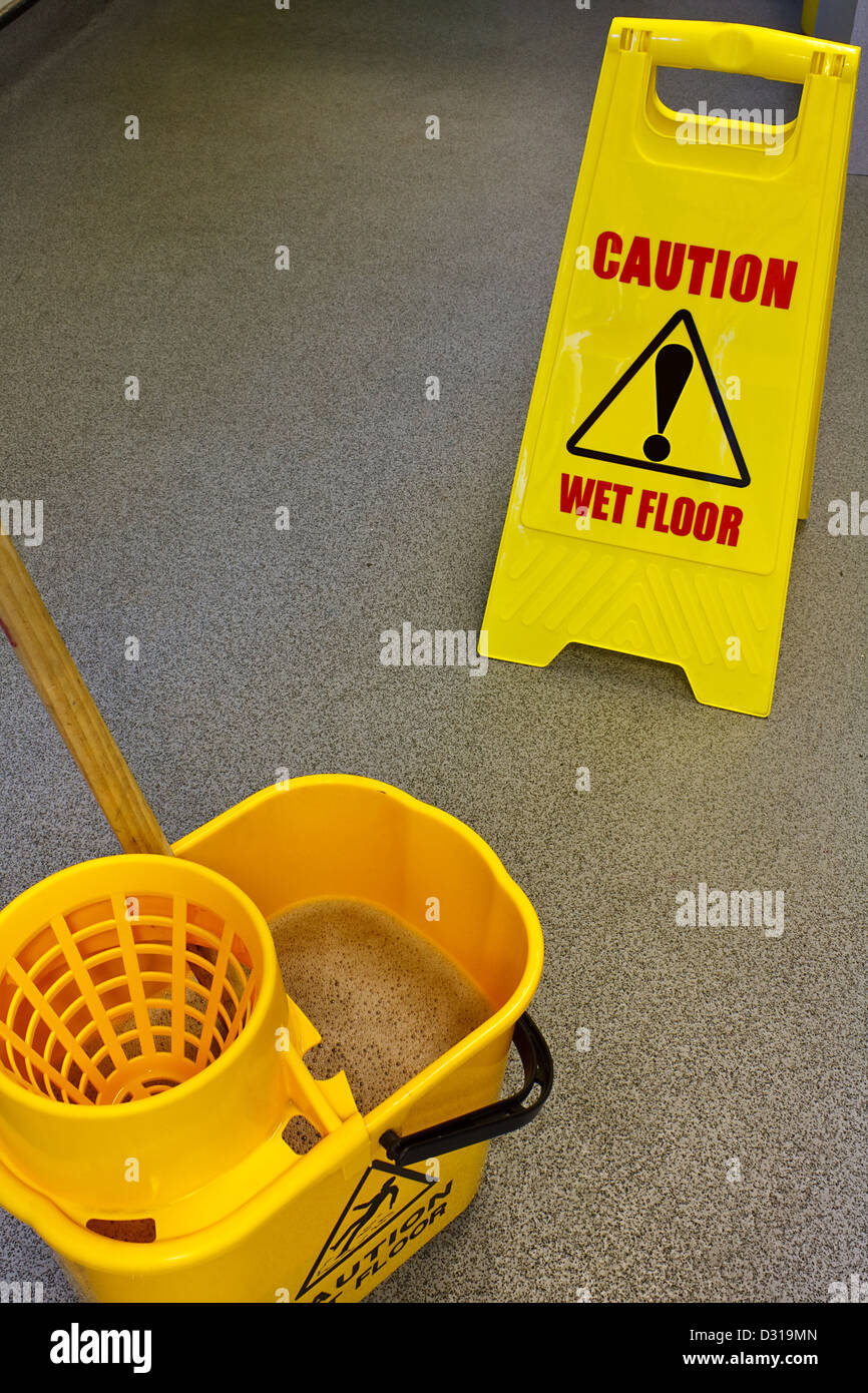 Caution wet floor health and safety sign with mop and bucket - Stock Image