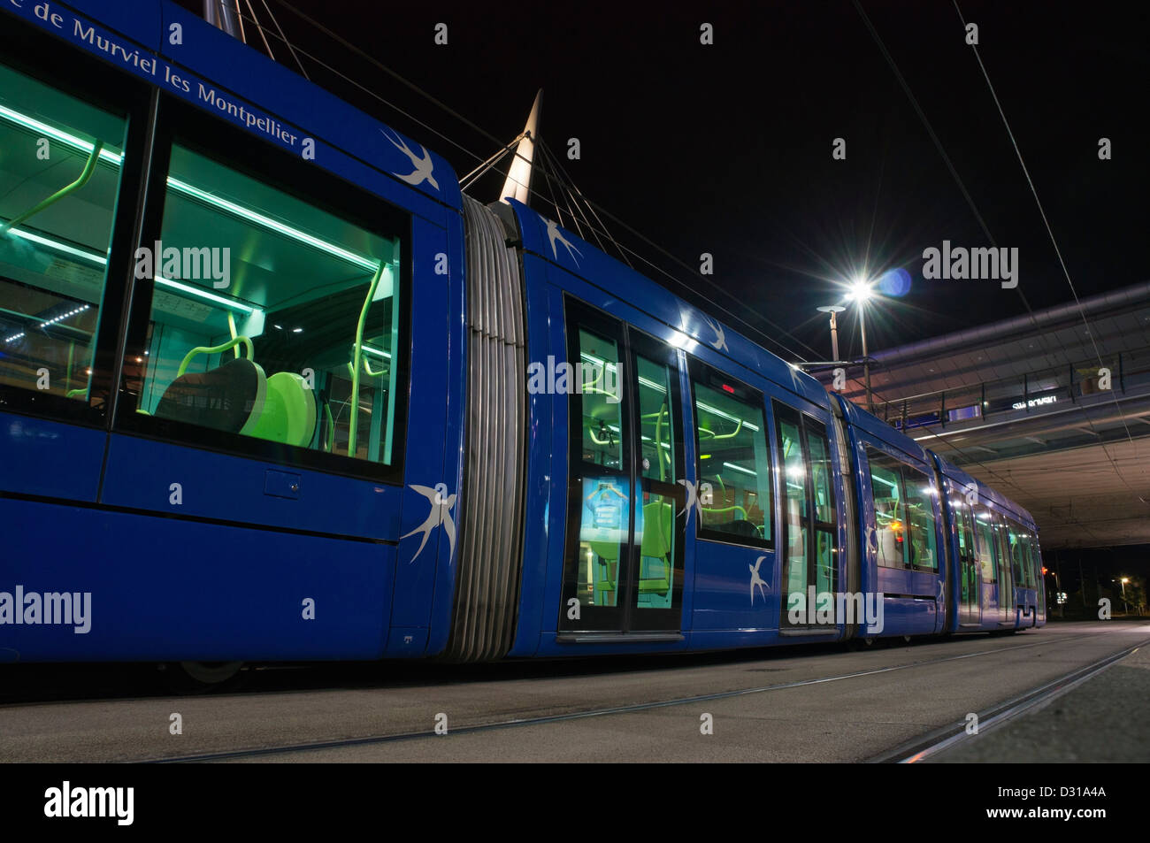 Tram at the quay, at night, Montpellier, France Stock Photo