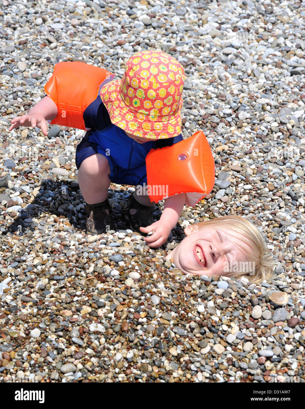A young boy covering his elder brother with pebbles on the beach - Stock Image