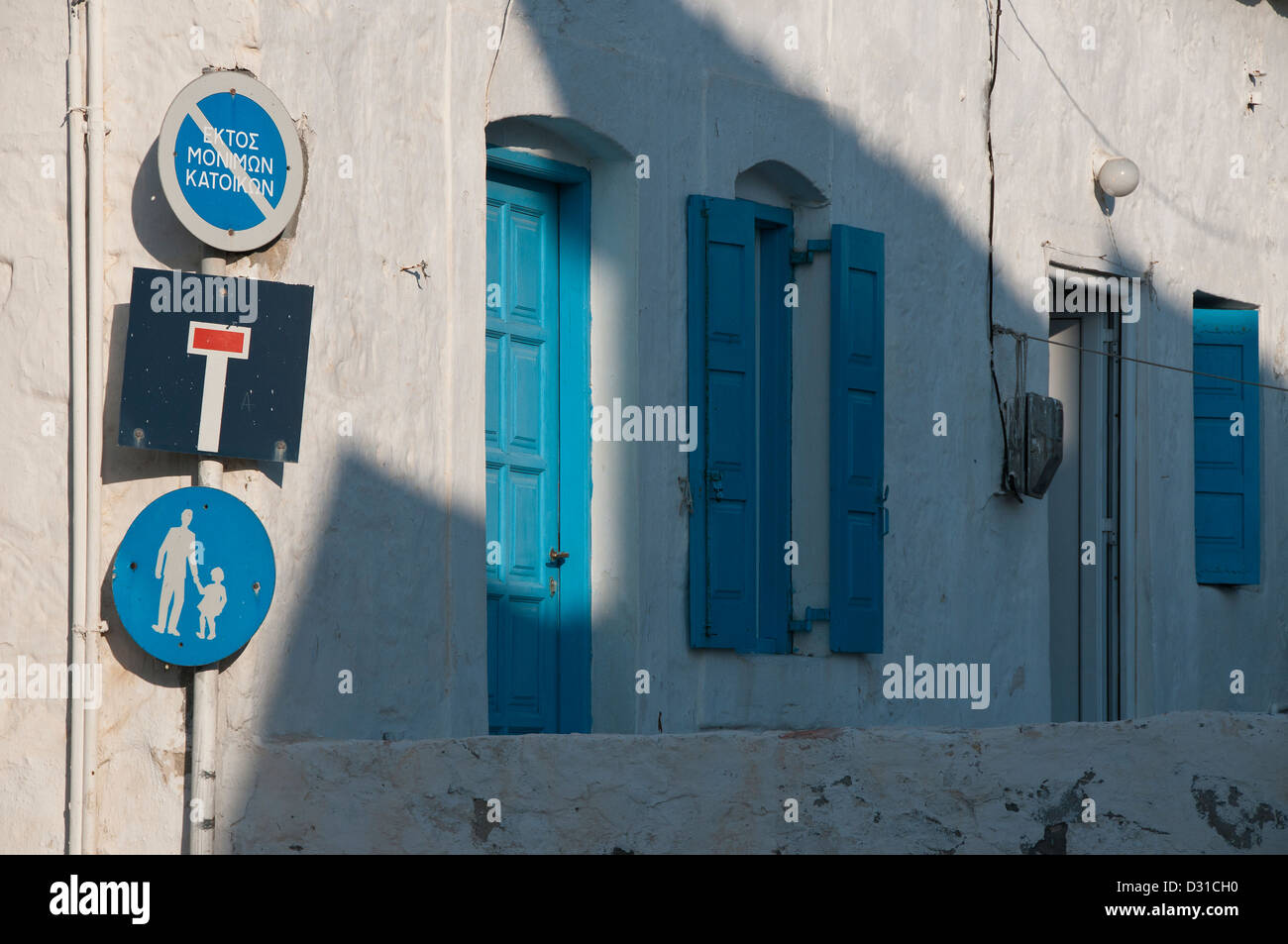 Greek road signs, blue shutters and doors. - Stock Image