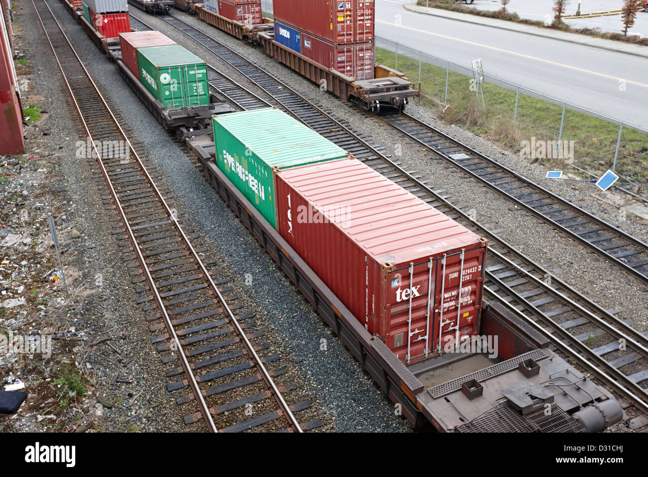 evergreen and tex freight shipping containers on rail cars freight train goods tracks Vancouver BC Canada Stock Photo