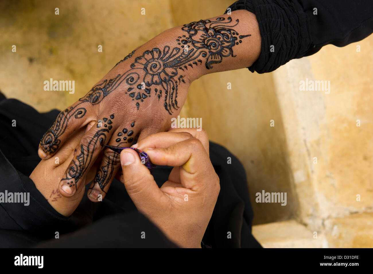 Swahili woman henna painting hands, Lamu, Lamu Archipelago, Kenya Stock Photo