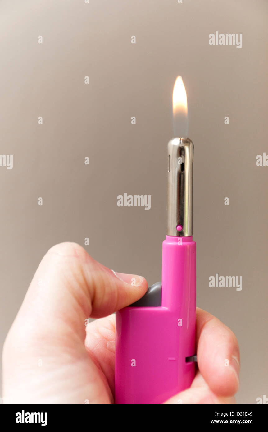 Small gas lighter with flame. - Stock Image