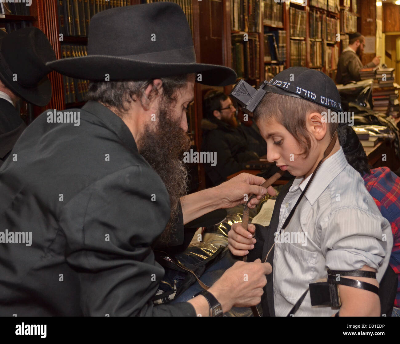 Father instructs his son in how to put on phylacteries (teffilin) in preparation for his Bar Mitzvah - Stock Image