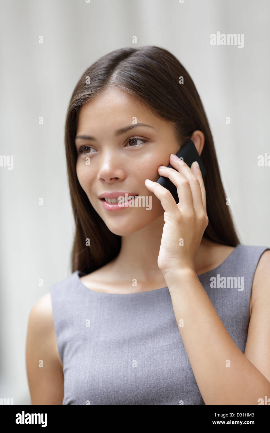 Beautiful young multiracial Caucasian / Asian Chinese professional woman talking on smartphone outside - Stock Image