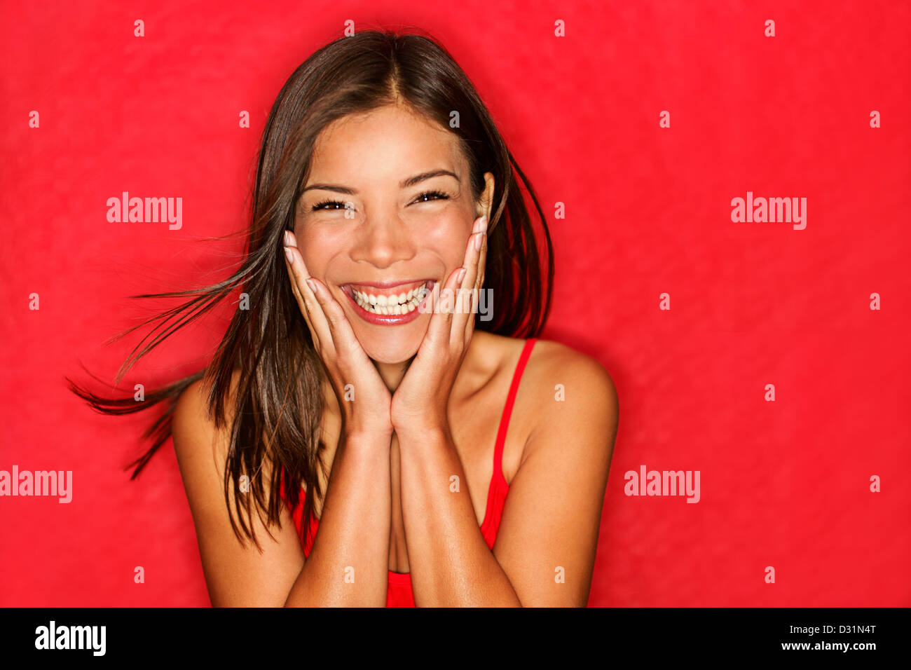 Portrait of funky young multicultural Caucasian / Chinese Asian woman holding head being amazed on red background - Stock Image