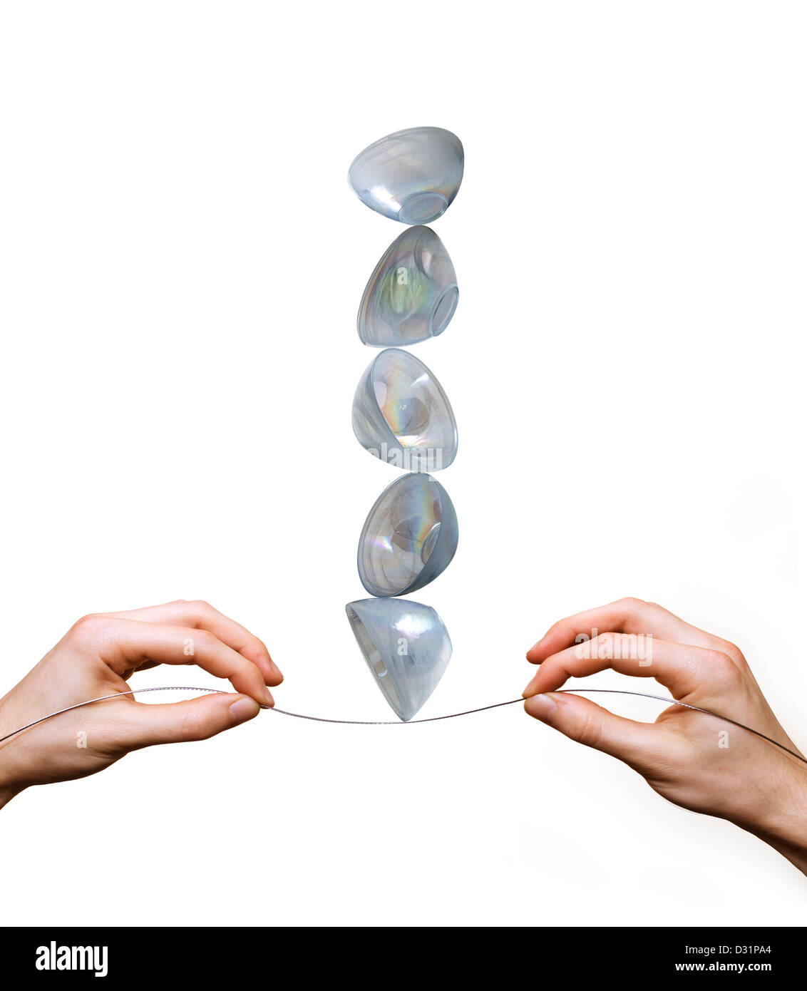 hands balancing stack of bowls on wire tightrope - Stock Image