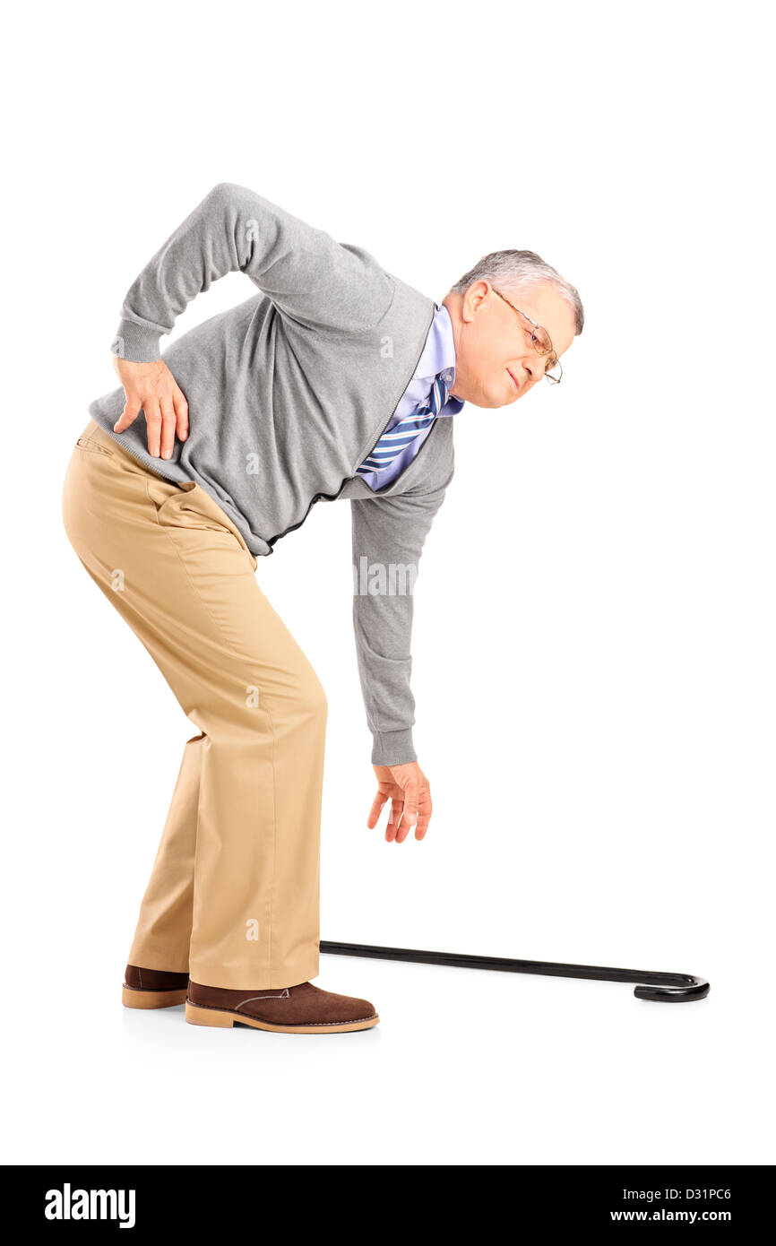 Full length portrait of a senior man with back pain trying to pick up a cane isolated on white background - Stock Image