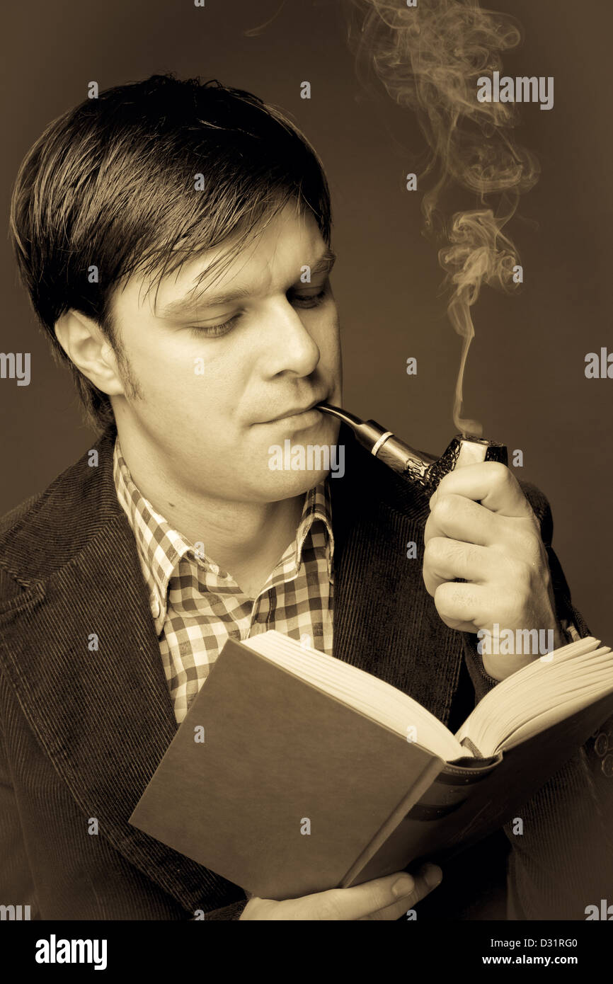 Portrait of a man reading and smoking a pipe. Close-up - Stock Image