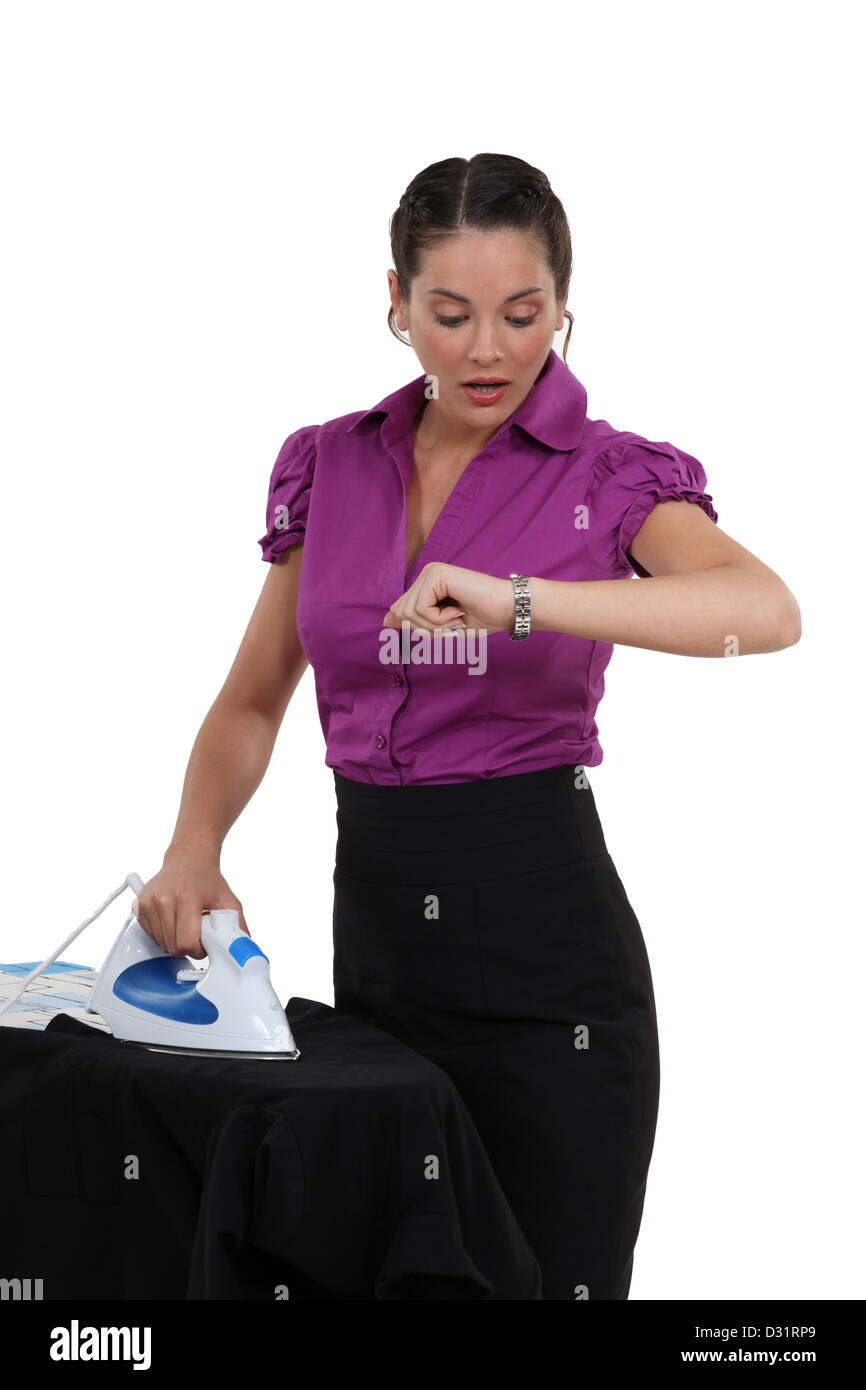 Woman ironing and watching the time go by - Stock Image