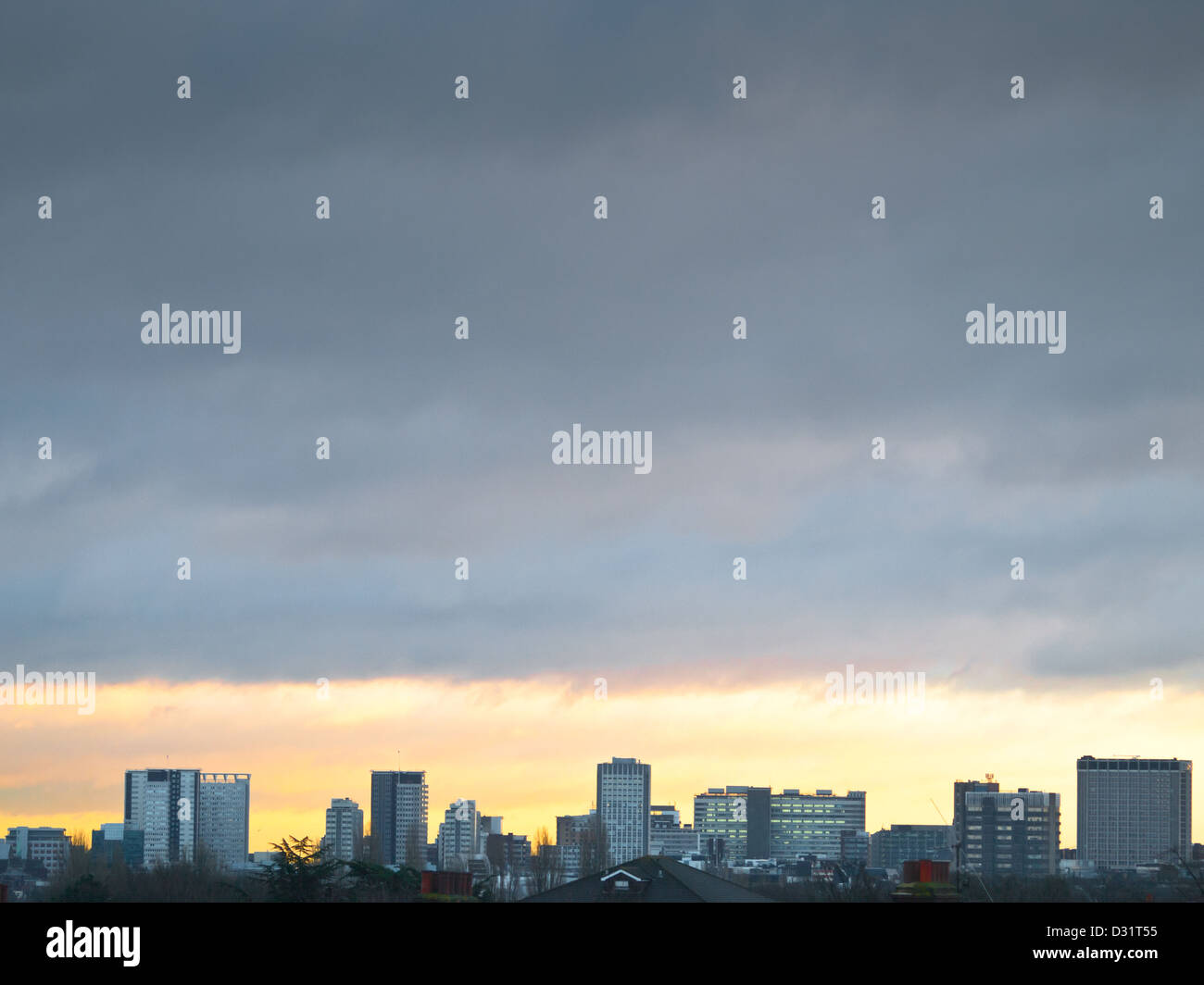 The cityscape of Croydon, south London, as the golden rays of dawn break through the thick grey clouds. - Stock Image