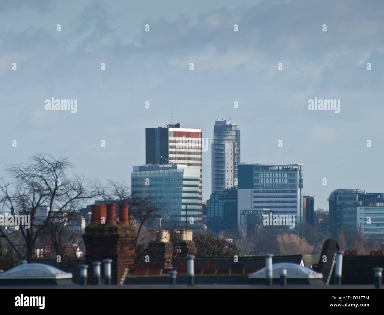 The architecture of central Croydon rises up above rooftops and chimney stacks. - Stock Image