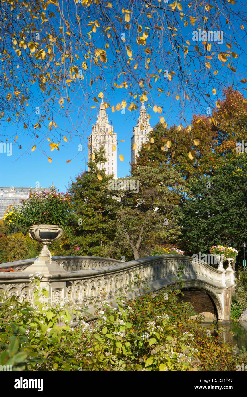 San Remo's twin towers behind the Bow Bridge, autumn in Central Park, New York, USA - Stock Image