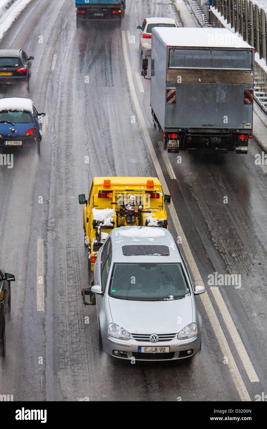 Traffic jam on German Autobahn, A40, after heavy snow fall. Breakdown service, towing car. - Stock Image