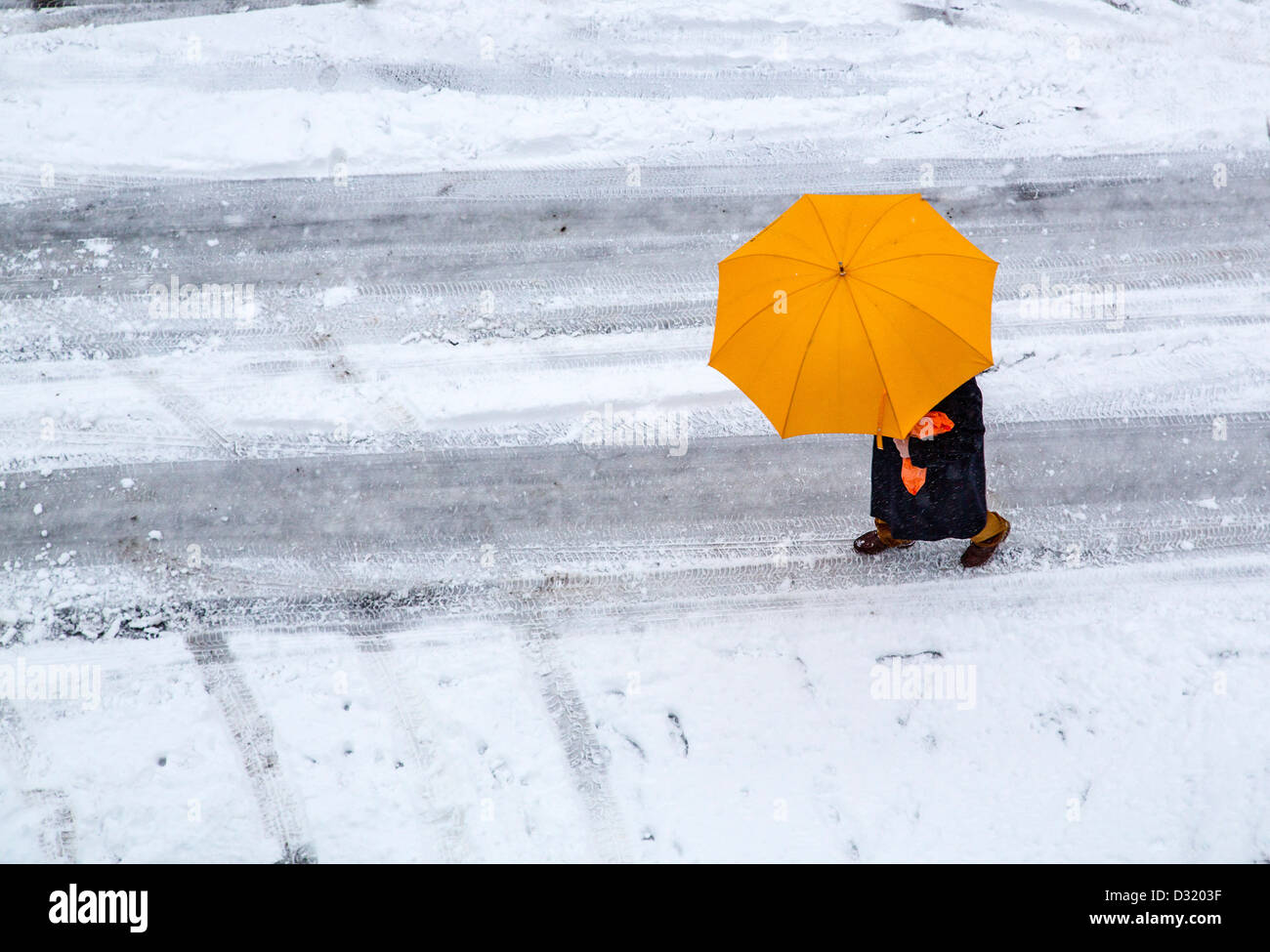 Person with a yellow umbrella walks on a snow covered street. - Stock Image