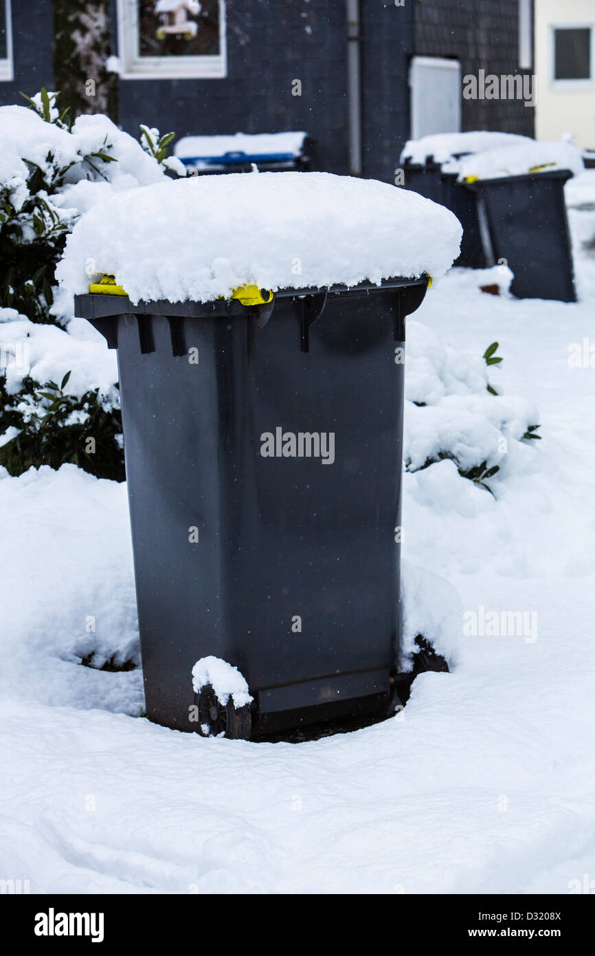 Snow covered garbage can. Due to heavy snow the garbage can was not emptied by rubbish collection services. - Stock Image