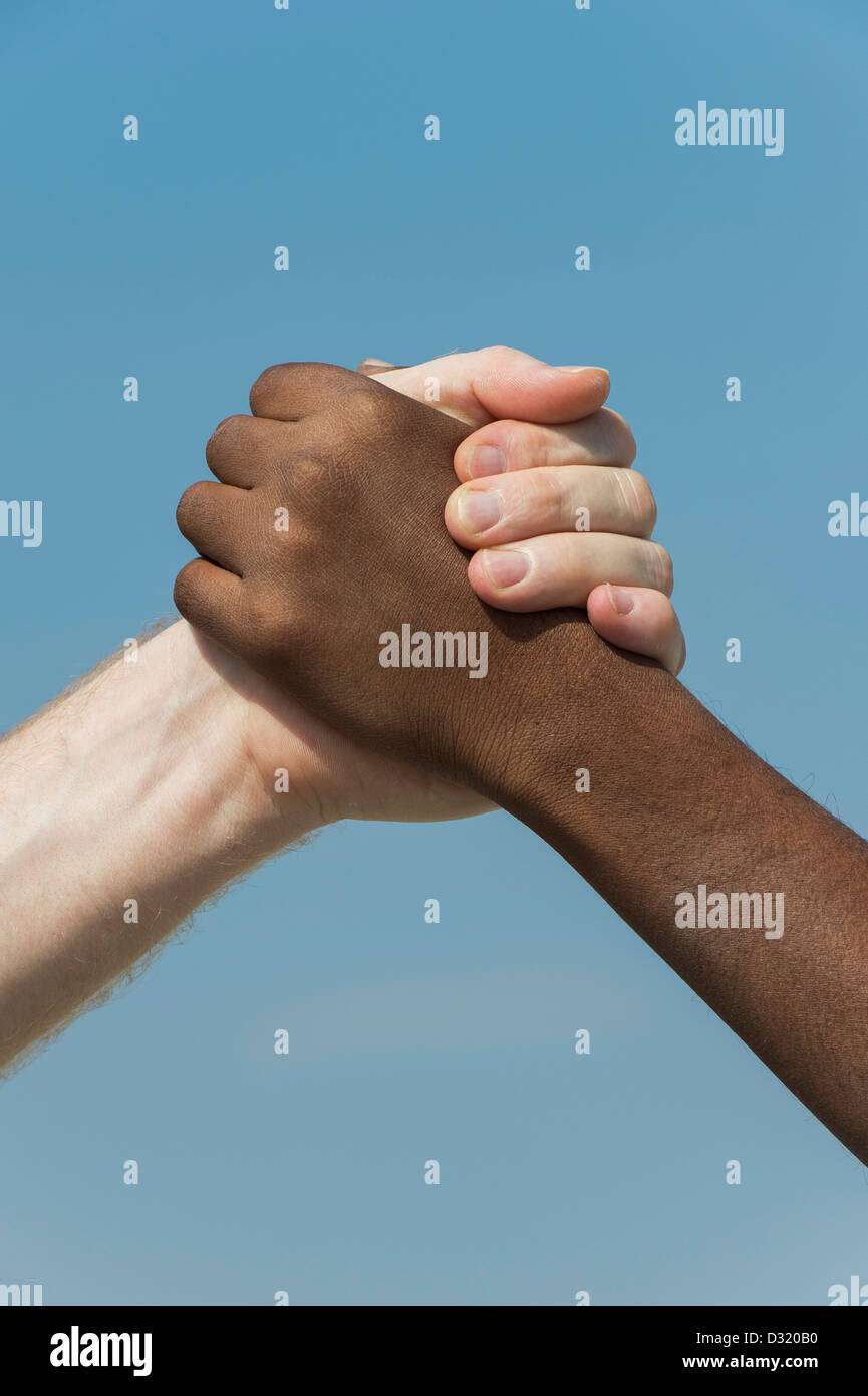Indian and English hands. Western and Eastern hand shake against a blue sky. india. One humanity concept. Stock Photo