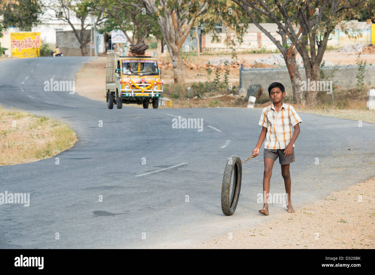 Indian boy playing with a tyre along an Indian road. Andhra Pradesh, India - Stock Image