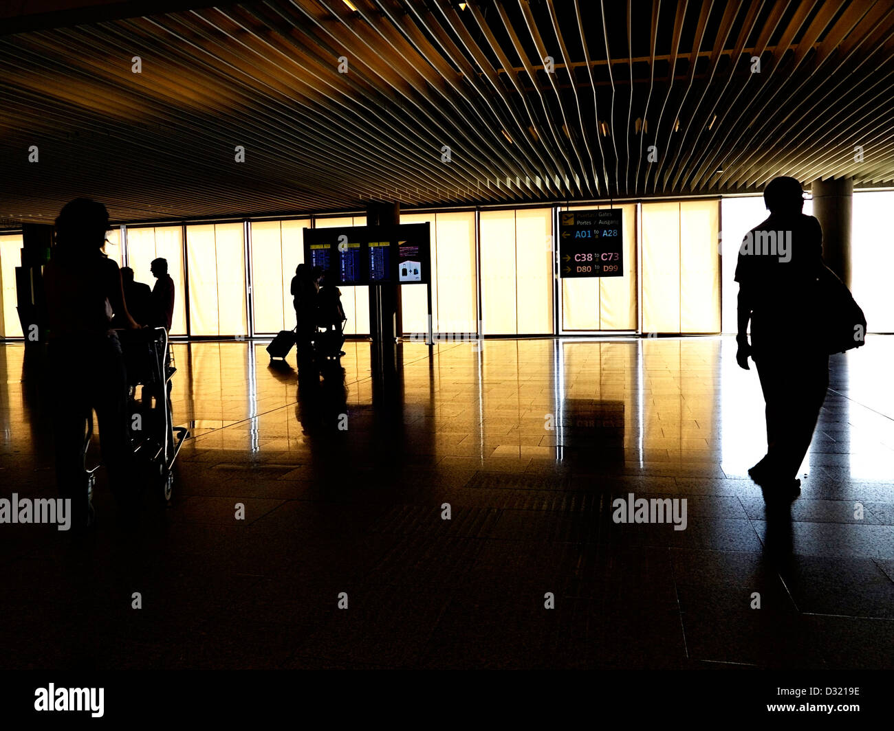 Passengers in an airport on their way to catch flights with screens showing departure information - Stock Image