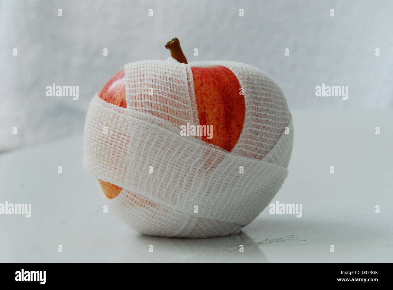 A red and yellow apple on a white background, wrapped in a white gauze bandage with an above, or birds eye view - Stock Image