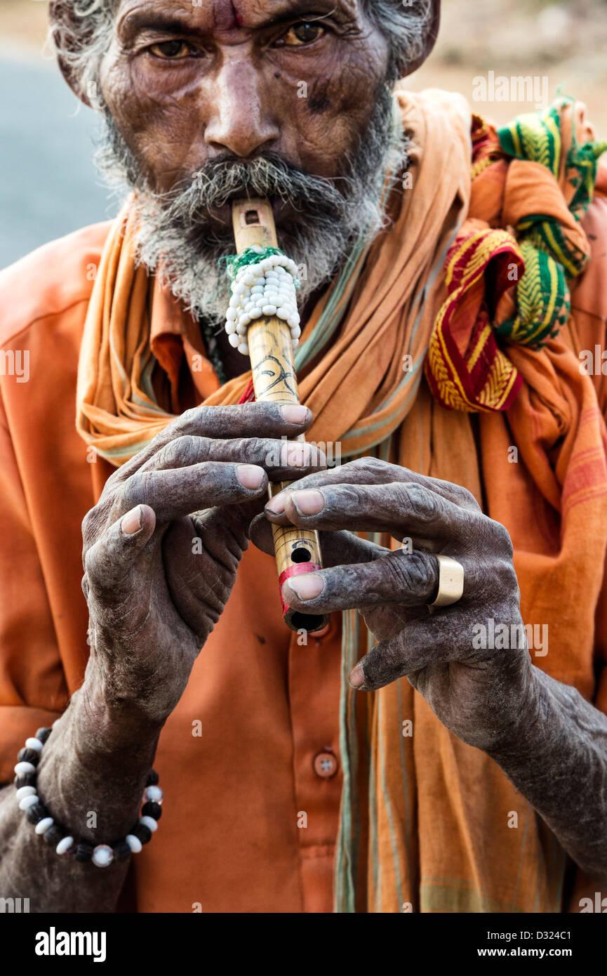Indian sadhu / beggar playing a flute portrait. Andhra pRADESH, India - Stock Image