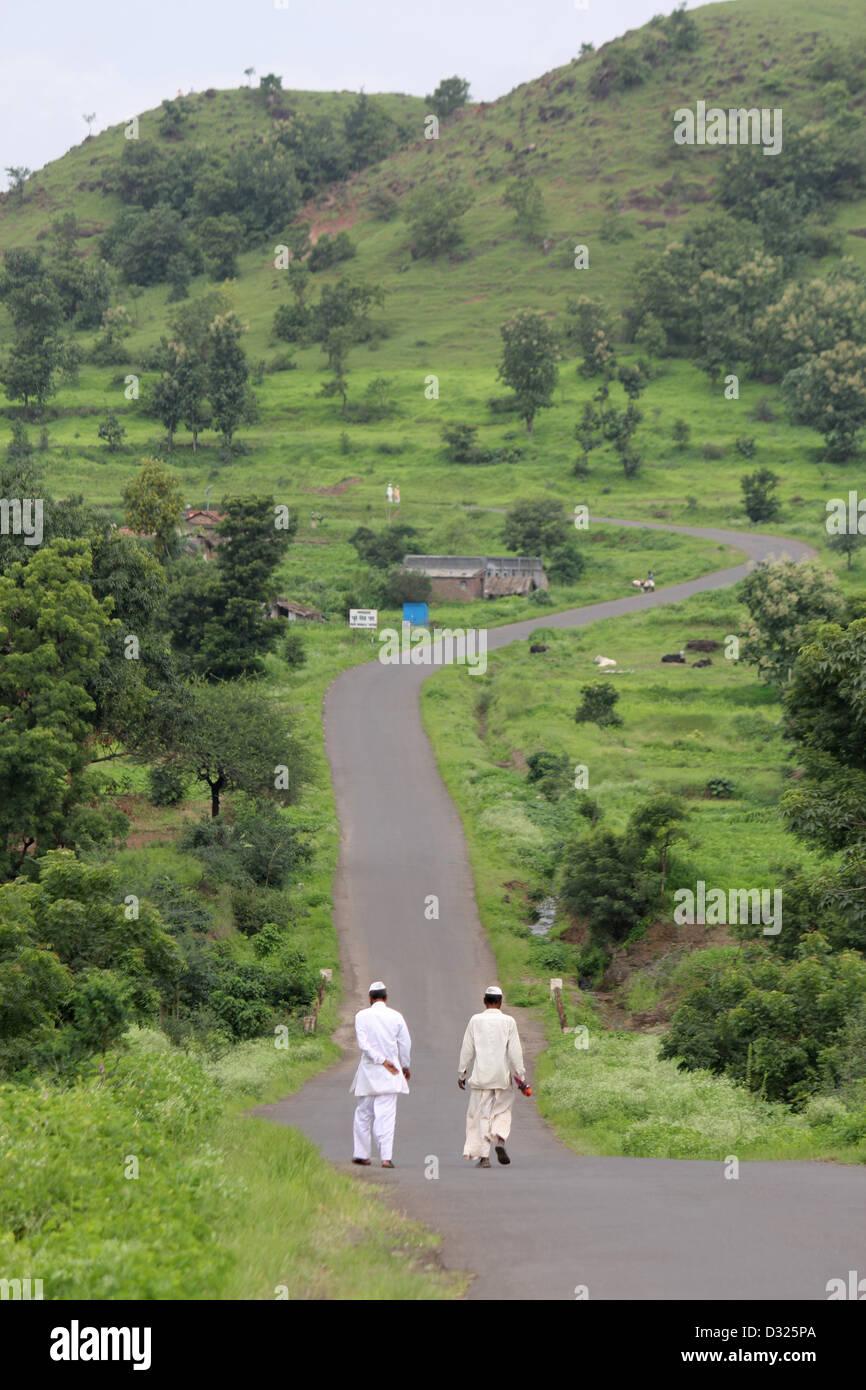 Two people walking on village road - Stock Image